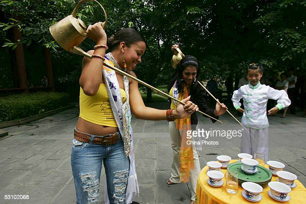 Contestants of 2005 Miss Tourism Queen International Miss Jamaica and Miss Sri Lanka learn to pour tea with traditional longmouth tea pots from a...