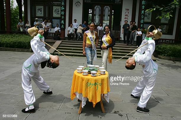 Contestants of 2005 Miss Tourism Queen International Miss Jamaica and Miss Sri Lanka watch Chinese children to perform pouring tea with traditional...