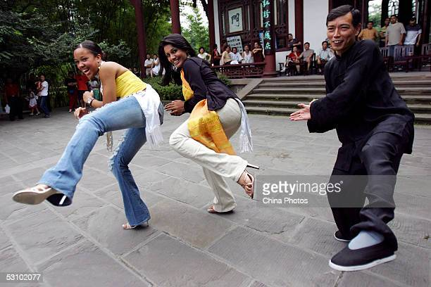Contestants of 2005 Miss Tourism Queen International Miss Jamaica and Miss Sri Lanka learn Chinese kung fu from a coach at a park during a...