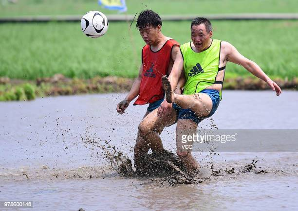 Contestants participate in a mud soccer game to cheer for the FIFA World Cup on June 18 2018 in Shenyang China
