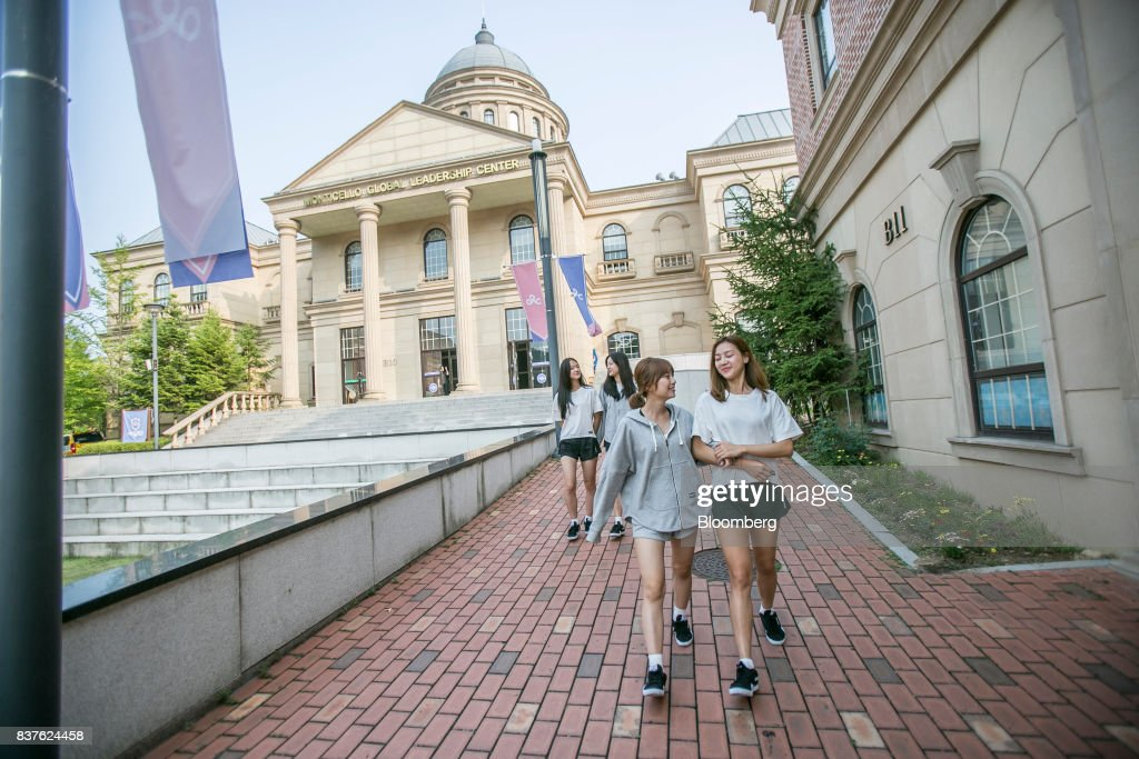 Contestants Yoo Ji-na, from left, Jang Gyu-ri, Cho Young-ju, and Tasha walk through Yangpyeong English School during the production of the 'Idol School' reality television show by CJ E&M Corp. in Yangpyeong, South Korea, on Thursday, June 29, 2017. Endless repetition, tear-inducing critiques from coaches, smile practice, and psychological counselling are plot points in an 11-week reality TV show documenting the creation of a teeny-bopper singing group. Idol School, which began airing in July, is part of a corporate push to turn Korean pop music into a global phenomenon. Photographer: Jean Chung/Bloomberg via Getty Images