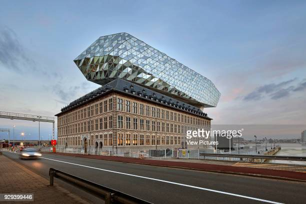 Contextual view from street at dusk Port House Antwerp Belgium Architect Zaha Hadid Architects 2016