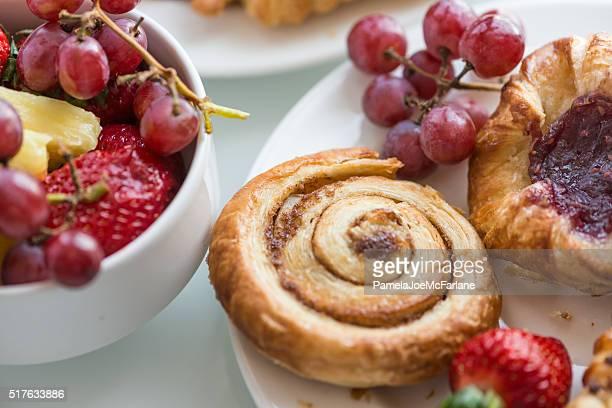 Kontinentales Frühstücksbuffet, das frisches Obst, Zimt Brötchen und dänischem Gebäck
