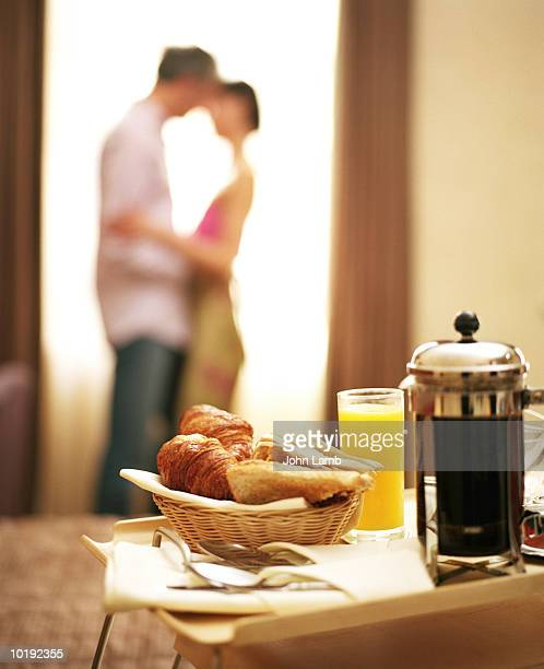Continental breakfast in hotel room, couple embracing in background (f