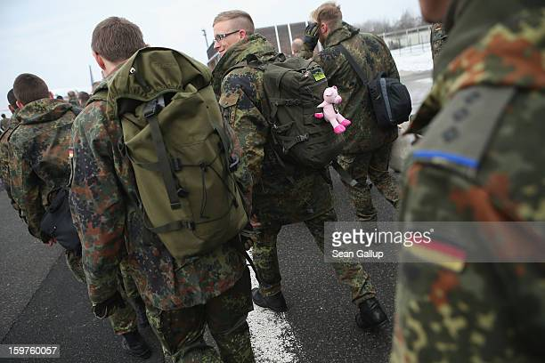 A contingent of approximately 240 soldiers of the German Bundeswehr including one with a stuffed pink pig attched to his rucksack prepare to board a...