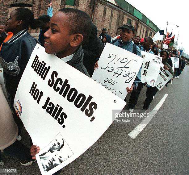 A contingent of students carry their signs as they march along the street from Gladstone Elementary School to Division XI of the Cook County...