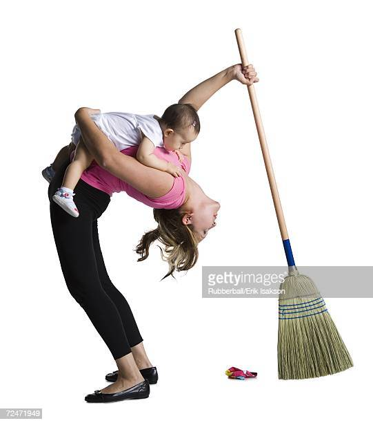 Contortionist mother sweeping while holding baby daughter