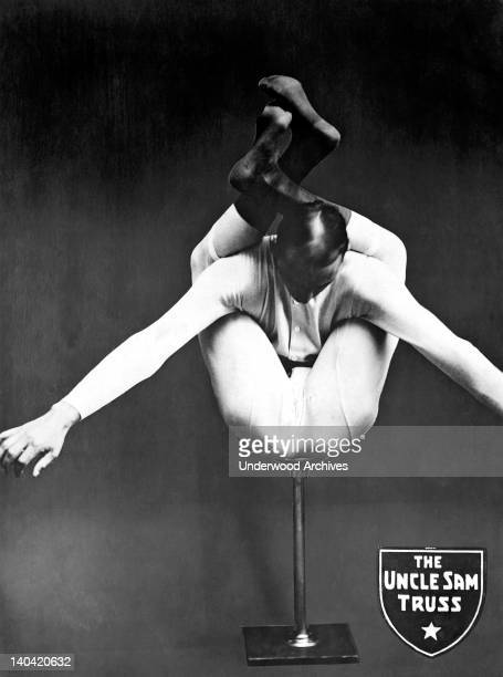 A contortionist puts his legs behind his back in an ad for the Uncle Sam Truss Company Buffalo New York circa 1920