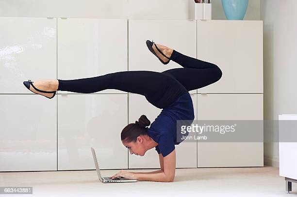 contortionist using laptop computer - contortionist stock pictures, royalty-free photos & images