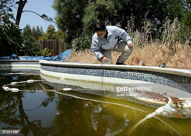 Contra Costa County Mosquito and Vector Control District technician Josefa Cabada inspects a neglected pool at a foreclosed home May 9 2008 in...