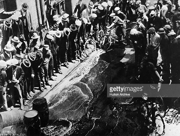 Contraband beer being spilled into the streets from barrels during the prohibition era
