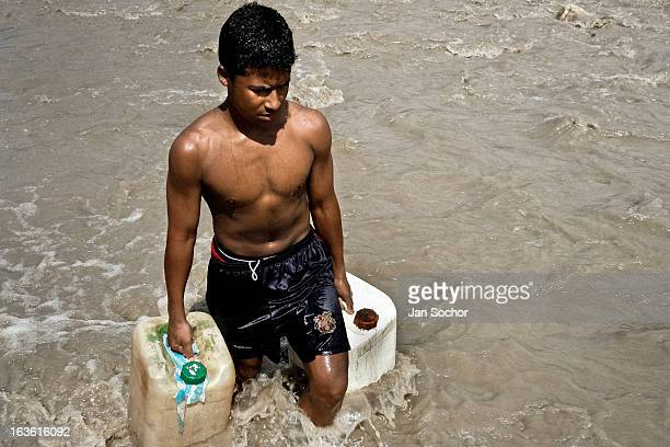 A contraband smuggler carries two barrels of gasoline across the river Tachira on the ColombiaVenezuela border on 2 May 2006 in La Parada Colombia...