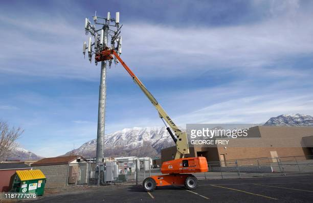 A contract crew for Verizon works on a cell tower in a school yard to update it to handle the new 5G network in Orem Utah on December 10 2019 The new...