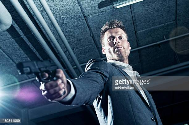 Contract killer points gun at someone