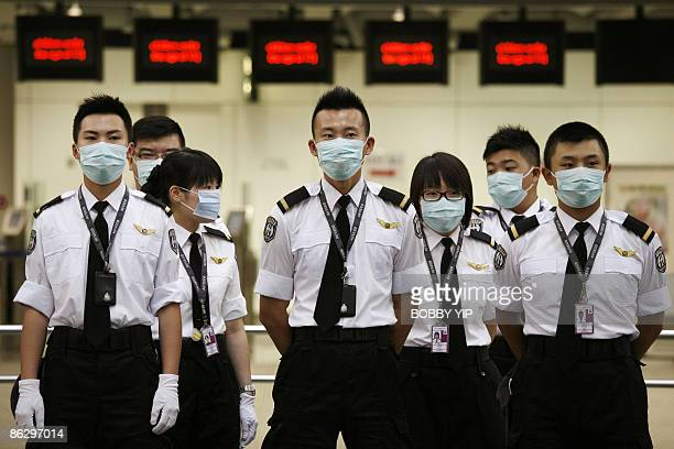 Contract staff of the Port Health department stand to attention before a shift change at the Hong Kong Airport ask passengers to fill in health...