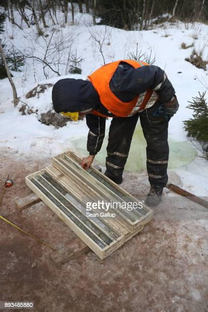 A contract worker for Deutsche Lithium GmbH looks at bore samples taken from 300 meters below the surface at a site on December 13 2017 at Zinnwald...