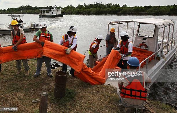 Contract workers load oil booms to protect marshlands along the Gulf of Mexico on May 13 2010 in Hopedale Louisiana The BP Deepwater Horizon oil rig...