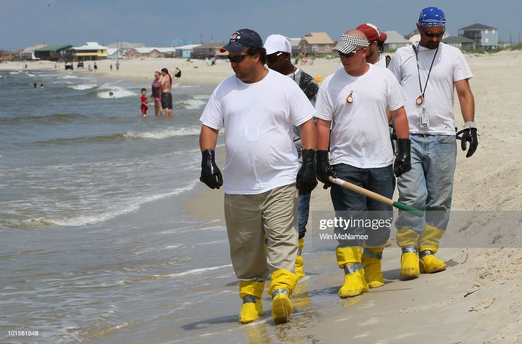 Contract workers patrol the beach to pick up oil that has wash ashore on a public beach on June 2, 2010 in Dauphin Island, Alabama. Oil believed to be from the Deepwater Horizon oil rig accident began to appear yesterday on the shores of Alabama.