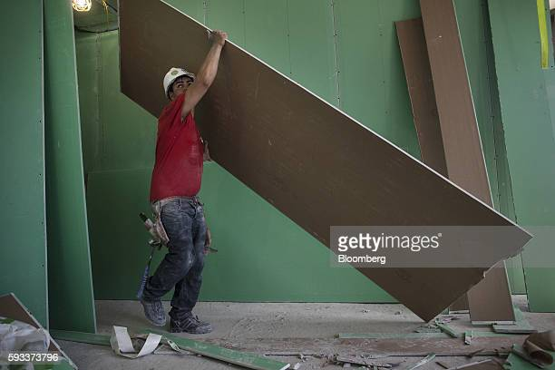 A contractor carries a panel of drywall in a unit under construction at the Toll Brothers Inc 100 Barrow Street residential building in New York US...