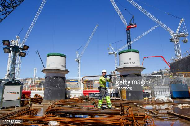 Contractor carries a reinforced steel bar near the cooling water pipes, in the base of the Turbine Hall within Reactor Unit One on the construction...