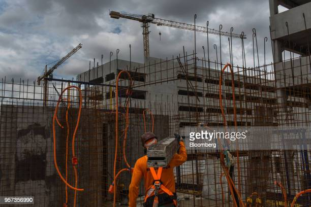 Contractor carries steel rods in front of mesh reinforcement panels during construction at the Reserva Paulista residential complex in Sao Paulo,...