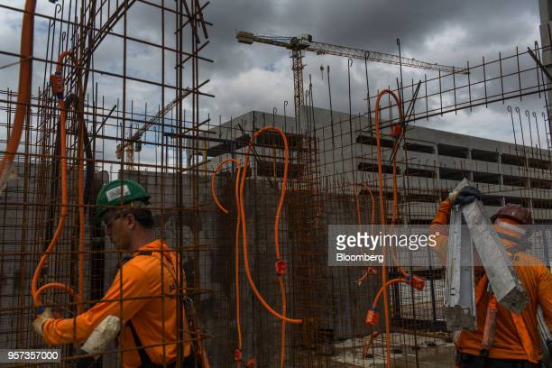 Contractor carries steel rods in front of mesh reinforcement panels at the Reserva Paulista residential complex under construction in Sao Paulo,...