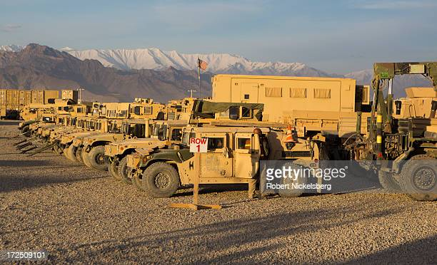 Contractor checks on a military vehicle at a sorting yard May 10, 2013 at Bagram Air Base, Afghanistan. The vehicles will be sent back to the U.S. Or...