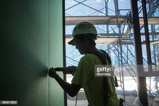 A contractor drills a panel of drywall in a unit under construction at the Toll Brothers Inc 100 Barrow Street residential building in New York US on...
