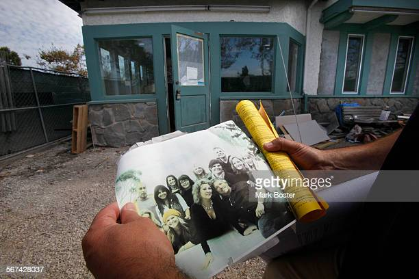 Contractor Fernando Dutra carries the faded photo of the staff and co–owners Sandy and Randy Fannin at Salon Meritage with his roll of permits and...