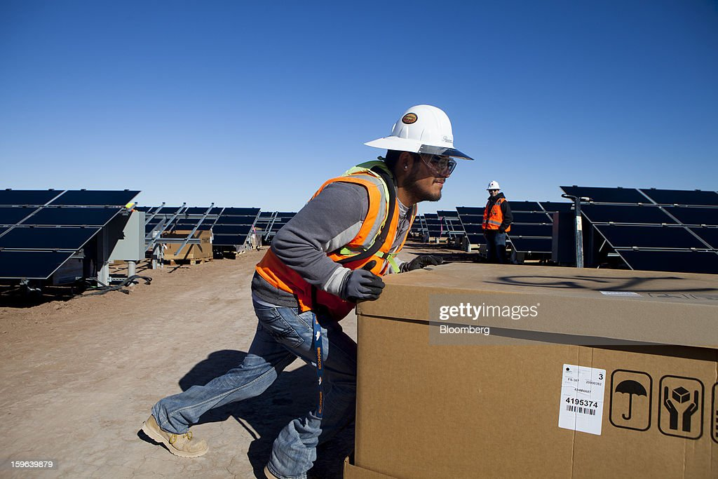A contractor for First Solar Inc. pushes a box of materials during construction of the Tenaska Imperial Solar Energy Center South project in Imperial County, California, U.S., on Thursday, Jan. 17, 2013. The Tenaska Imperial Solar Energy Center South, when completed, will be a ground-mounted photovoltaic solar power generating system producing enough energy to meet the needs of at least 44,000 California homes, according to the Tenaska web site. Photographer: Sam Hodgson/Bloomberg via Getty Images