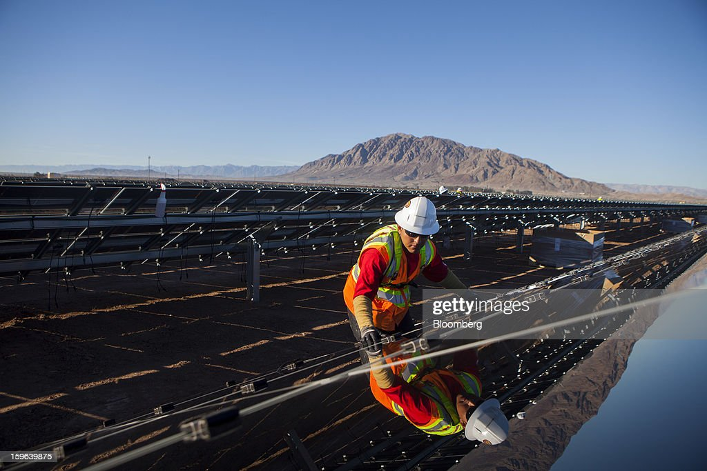 A contractor for First Solar Inc. work on construction of the Tenaska Imperial Solar Energy Center South project in Imperial County, California, U.S., on Thursday, Jan. 17, 2013. The Tenaska Imperial Solar Energy Center South, when completed, will be a ground-mounted photovoltaic solar power generating system producing enough energy to meet the needs of at least 44,000 California homes, according to the Tenaska web site. Photographer: Sam Hodgson/Bloomberg via Getty Images