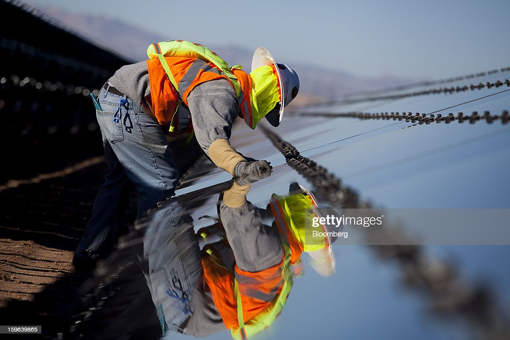 A contractor for First Solar Inc. works on construction of the Tenaska Imperial Solar Energy Center South project in Imperial County, California, U.S.,, on Thursday, Jan. 17, 2013. The Tenaska Imperial Solar Energy Center South, when completed, will be a ground-mounted photovoltaic solar power generating system producing enough energy to meet the needs of at least 44,000 California homes, according to the Tenaska web site. Photographer: Sam Hodgson/Bloomberg via Getty Images