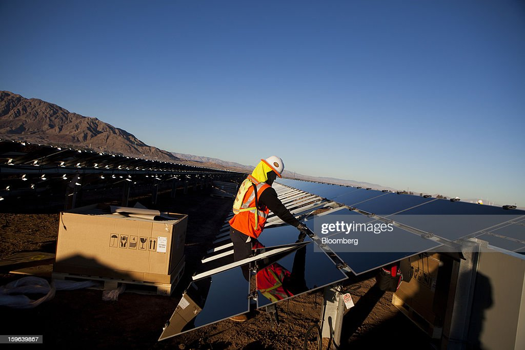 A contractor for First Solar Inc. works on construction of the Tenaska Imperial Solar Energy Center South project in Imperial County, California, U.S., on Thursday, Jan. 17, 2013. The Tenaska Imperial Solar Energy Center South, when completed, will be a ground-mounted photovoltaic solar power generating system producing enough energy to meet the needs of at least 44,000 California homes, according to the Tenaska web site. Photographer: Sam Hodgson/Bloomberg via Getty Images