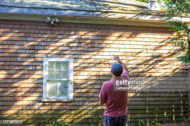 contractor gesturing, pencil in hand, at roof line of old barn. - catherine ledner stock pictures, royalty-free photos & images