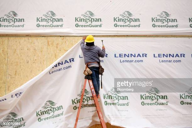 A contractor hammers building wrap onto a house under construction at the Lennar Corp Tree Tops community development in Lancaster South Carolina US...