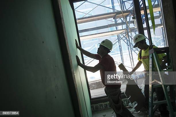 A contractor hangs a panel of drywall in a unit under construction at the Toll Brothers Inc 100 Barrow Street residential building in New York US on...