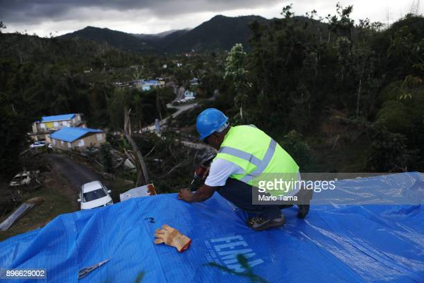 A contractor helps apply a FEMA tarp to a home damaged by Hurricane Maria on December 20 2017 in Morovis Puerto Rico Barely three months after...