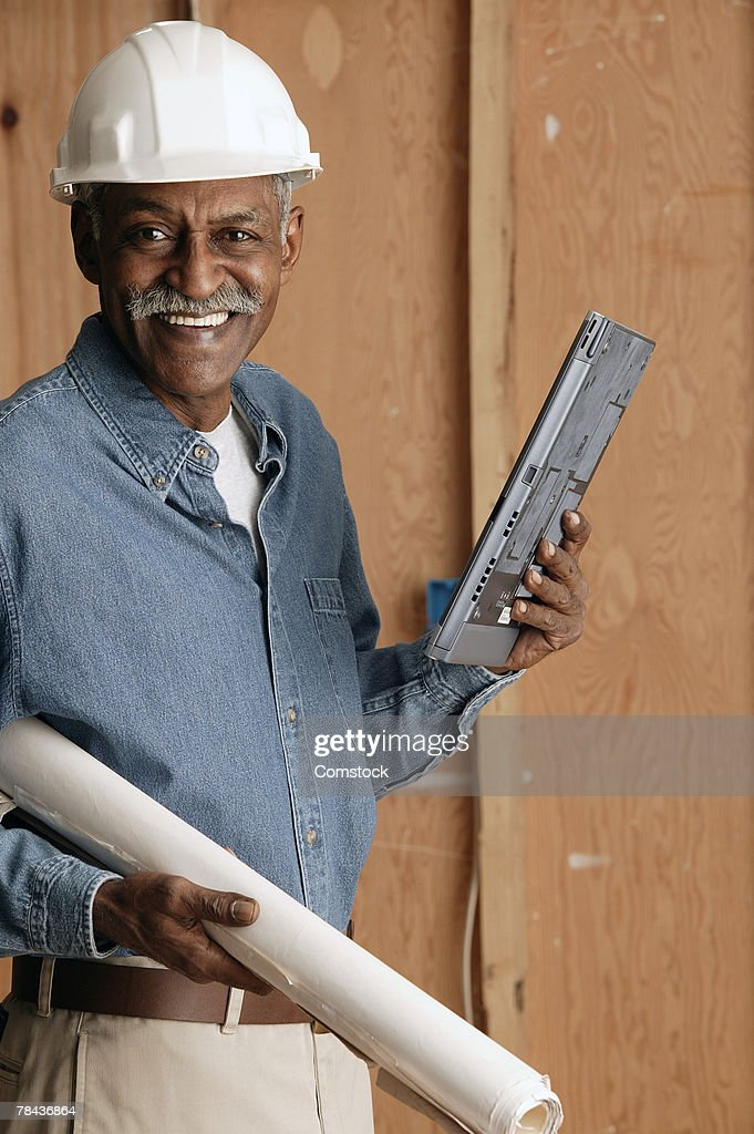 Contractor holding blueprints and laptop computer : Stockfoto