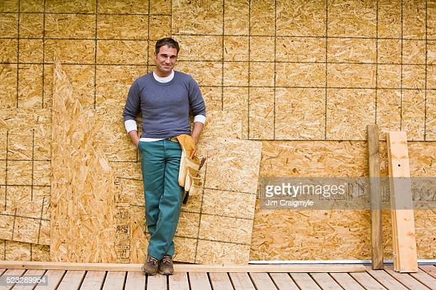 contractor leaning on wall of home under renovation - builder stock photos and pictures