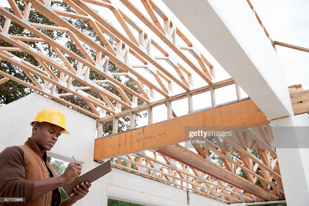 Contractor making notes at green building site : Stock Photo