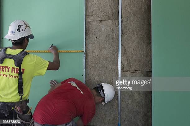 A contractor measures a panel of drywall in a unit under construction at the Toll Brothers Inc 100 Barrow Street residential building in New York US...