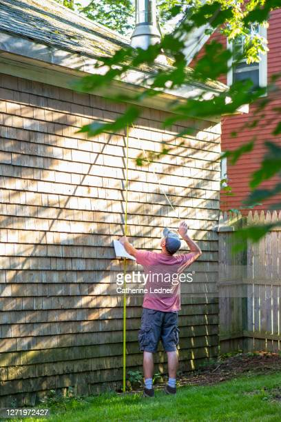 contractor measuring the height of an old wood shingled barn in need of repair - catherine ledner stock pictures, royalty-free photos & images