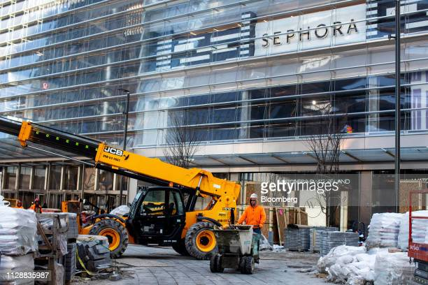 A contractor moves material during construction outside the retail entrance at the Hudson Yards development in New York US on Tuesday March 5 2019...