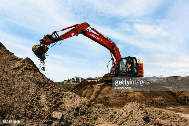 A contractor operates a Hitachi Ltd track excavator at a construction site in Whitby Ontario Canada on Wednesday May 10 2017 Ontario officials...