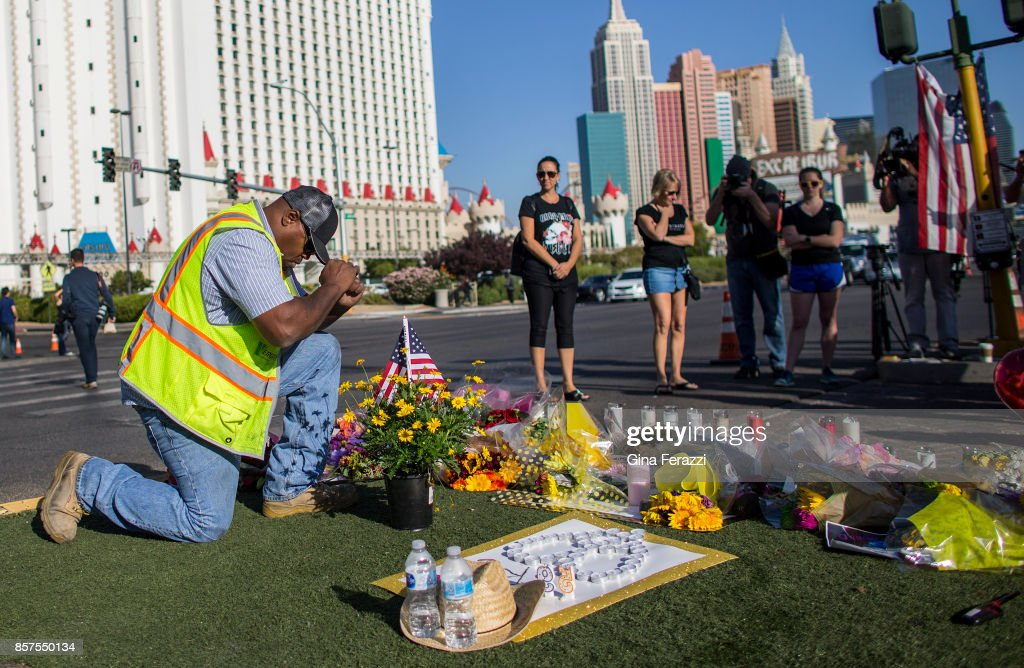 Contractor Robert Walker says a prayer after placing flowers and American flag at the scene of a memorial for the victims of the mass shooting on Las Vegas Boulevard near the crime scene on October 4, 2017 in Las Vegas, Nevada.