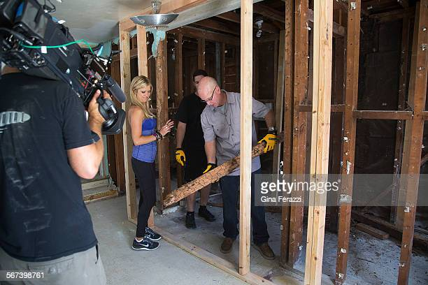 Contractor Steve Cederquist shows husband and wife team Christina and Tarek El Moussa a termite invested support beam during the filming of an...