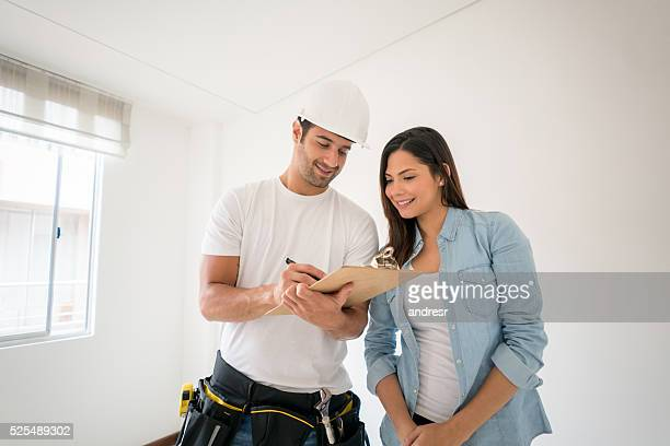 contractor talking to a woman at home - building contractor stock pictures, royalty-free photos & images