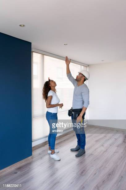 contractor talking to a woman while repairing her house - ceiling stock pictures, royalty-free photos & images