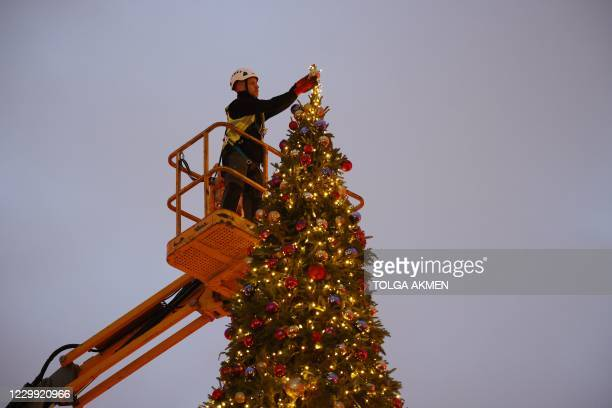 Contractor uses a cherrypicker to place final decorations on a 40ft Christmas tree during a photo call in the courtyard of Somerset House in London...