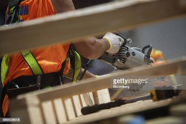 A contractor uses a circular saw to cut lumber while working on the construction site of a residential building in New York US on Thursday Aug 11...